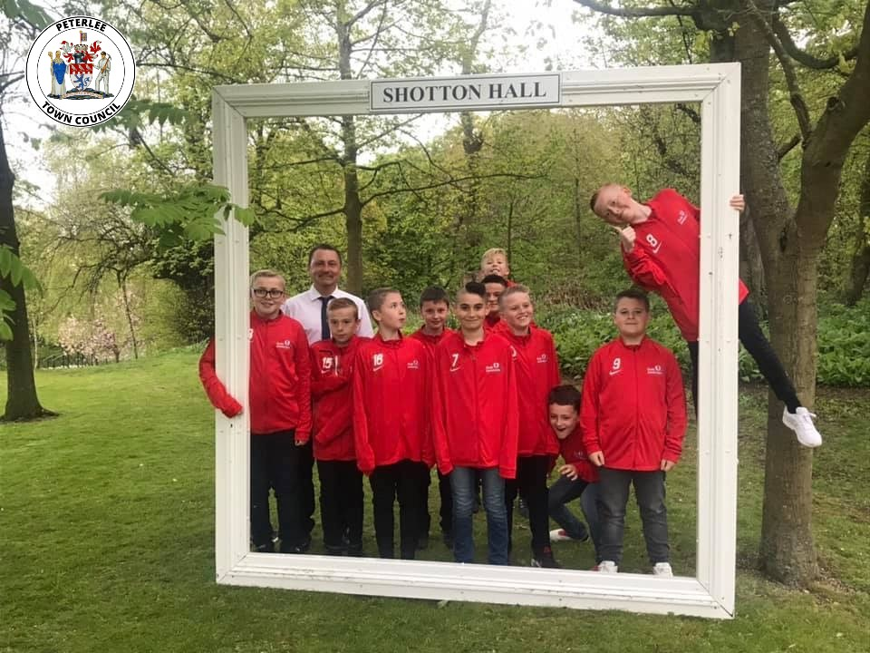 A photo of the Bradley Improtech footbal club with their coach, Michael Eggleston