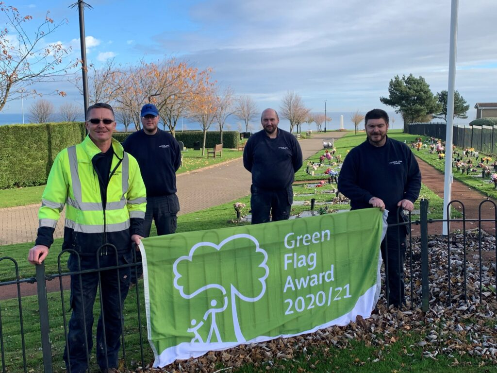 Cemetery Team stood with a banner displaying their awarded green flag status
